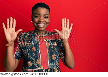 Young african american woman wearing african style showing and pointing up with fingers number ten while smiling confident and happy.