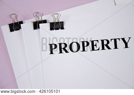 Property Concept Written On White Piece Of Paper And Pink Background
