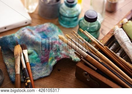 Oil painting preparation. Old painting brushes and equipment  on an old painters desk.