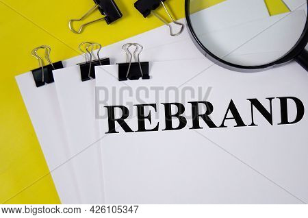Rebrand Word Written On White Paper And Yellow Background With Magnifier