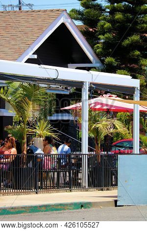 July 6, 2021 In Long Beach, Ca:  People Dining On An Outdoor Patio With Seating At A Restaurant In A