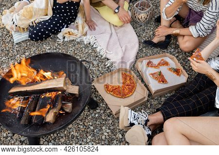 People By The Bowl With Fire Having A Picnic, Close-up View From Above On Fire And Pizza