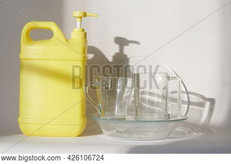 Yellow Plastic Canister With Pump Dispenser And Cleaning Disinfectant Liquid Stands Next To A Clean
