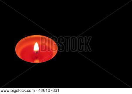 Lit Red Candle On A Black Background. Copy Space.