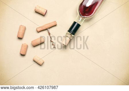 Flat Lay Incomplete Bottle Of Red Wine With Cork And Corkscrew On Beige Concrete Background. Top Vie