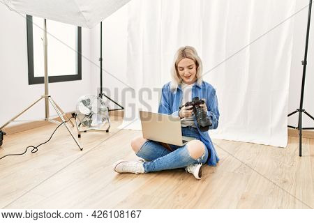 Beautiful blonde woman working as professional photographer at photography studio sitting on the floor checking photos on computer laptop
