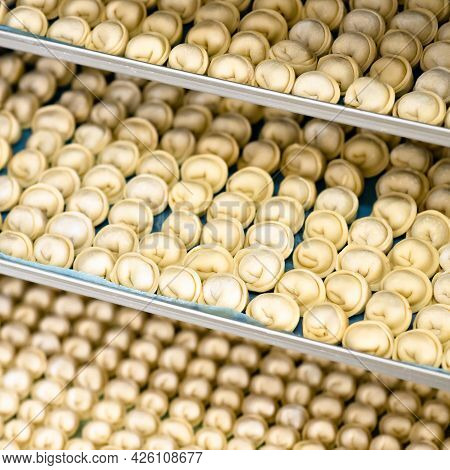 Rows Of Raw Dough Product, Ravioli Or Dumplings On Trays Or Freezer Shelves. Convenience Food. Backg
