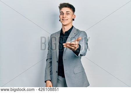 Young caucasian boy with ears dilation wearing business jacket smiling cheerful offering palm hand giving assistance and acceptance.