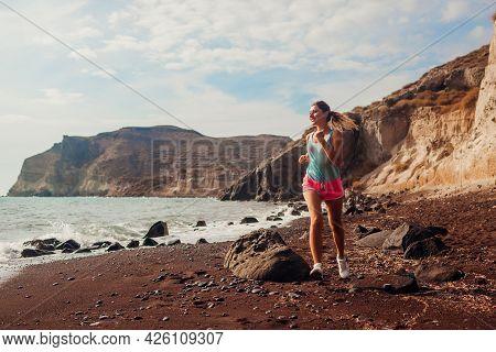Woman Running On Red Beach On Santorini Island. Female Runner Jogging During Outdoor Workout Enjoyin
