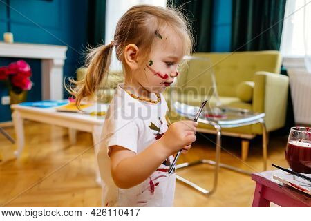 Funny Girl In White T-shirt And Stained Clothes Painting With Watercolors, Child Himself Dirty Hands