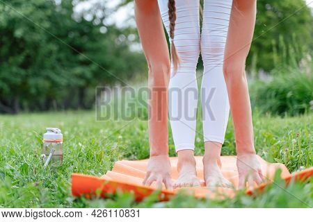 Slim Young Woman Doing Yoga In The City Park