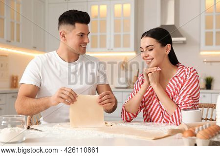 Happy Couple Wearing Pyjamas And Cooking Together In Kitchen