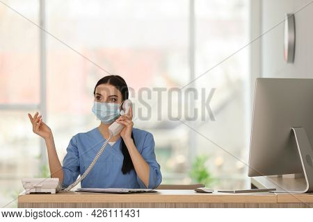 Receptionist With Protective Mask Talking On Phone At Countertop In Hospital
