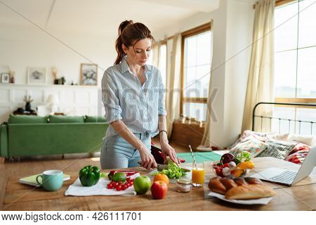 A Young Woman Reads A Recipe Online On Her Laptop. Cooking Lunch With Fresh Vegetables.