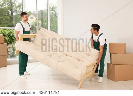 Professional Movers Carrying Sofa In New House