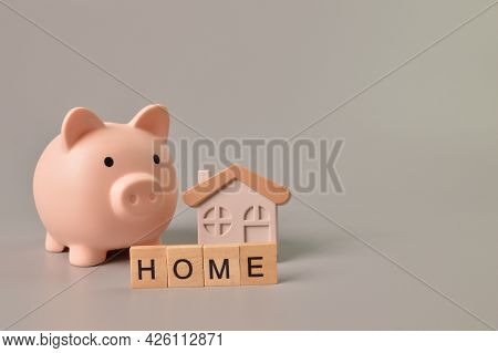 Piggy Bank, Toy House And Wooden Blocks With Text Home.