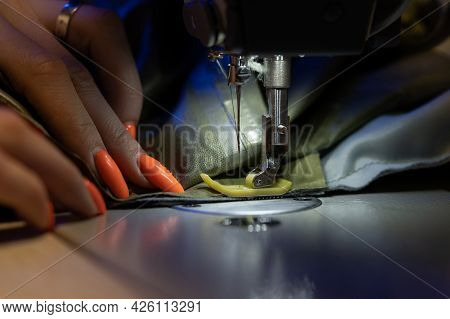 Closeup Of Seamstress Sew Clothes On Sewing Machine. Work With Light Of Hardware Lamp. Female Hand H