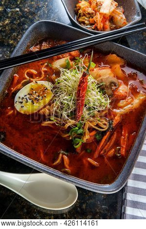 Korean Kimchi Ramen Garnished With Mushrooms Scallions And A Softboiled Egg With Black And White Ses