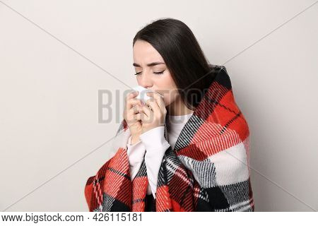Young Woman With Blanket Suffering From Runny Nose On Beige Background