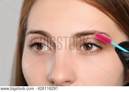 Beautician Brushing Woman's Eyebrows Before Tinting On Grey Background, Closeup