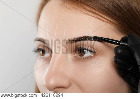Beautician Applying Tint During Eyebrows Correction Procedure On Grey Background, Closeup