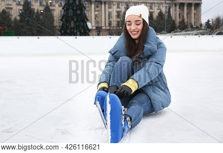 Woman Adjusting Figure Skate While Sitting On Ice Rink. Space For Text