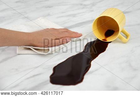 Woman Cleaning Spilled Coffee On White Marble Table, Closeup