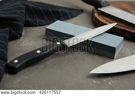 Sharpening Stone And Knives On Grey Table, Closeup