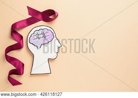 Human Head Cutout With Brain Near Purple Ribbon On Beige Background, Flat Lay. Epilepsy Awareness