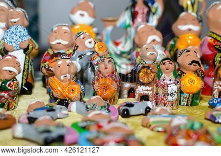 Traditional Ceramic Figurines Of Happy Uzbek Men And Women In National Clothes With Bread In Hands