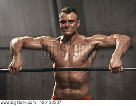 Smiling Male Athlete Doing Pull Ups On Bar During Cross Fit Training In Gym