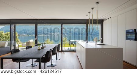 Interior of a modern apartment, with dining room and open kitchen. Front view. While eating you have a spectacular view of the lake. Nobody inside, the table seats six.