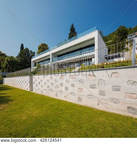Exterior of a modern house, you can see the garden and a beautiful stone and concrete wall