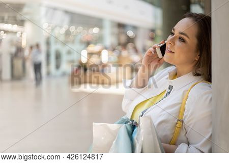 Closeup Buyer Woman Talking Smartphone Smiling Holding Bags With Purchasing At Shopping Mall