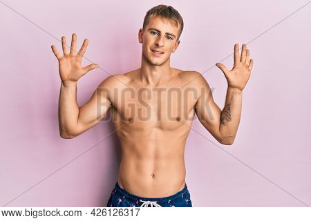 Young caucasian man wearing swimwear showing and pointing up with fingers number ten while smiling confident and happy.