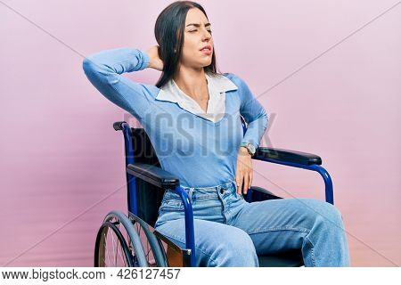 Beautiful woman with blue eyes sitting on wheelchair suffering of neck ache injury, touching neck with hand, muscular pain