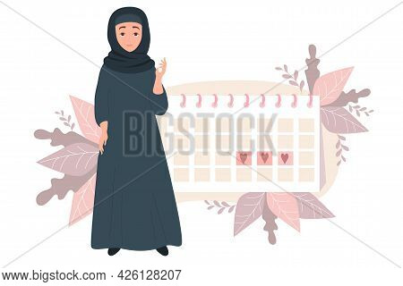 Girl Looking At Calendar. Beautiful Muslim Woman Wearing Hijab. Stands Near The Female Health And Me