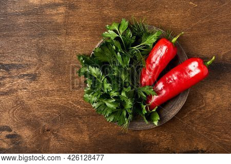 Red Pepper And Parsley On Ceramic Plate On Wooden Brown Background, Top View