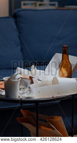 Empty Home Of Depressed Person With Messy Table With Leftover Thrown On Floor In Unorganized Living