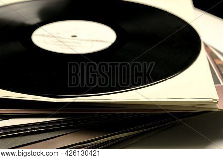 A Stack Of Old Vinyl Records Close Up One Of The Records Is Taken Out Of The Envelope