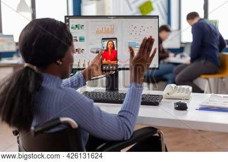 African Disabled Worker Waving At Online Partner During Video Call Sitting Immobilized In Wheelchair