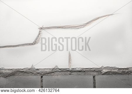Industrial Background. Old Brick Wall With Peeling Stucco. Weathered Rough Wall Surface With Brickwo