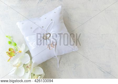 Pillow For Wedding Rings With Rings With Rhinestone Hearts And White Orchid On A White Texture Backg