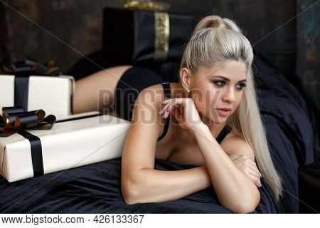 A Girl With Long Straight Hair Alone With A Gift Box In A Dark Bedroom. Young Woman In Lingerie Earl
