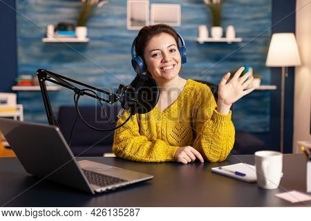 Social Media Influencer Smiling At Camera Sitting In Home Studio Ready For Streaming New Podcast. On