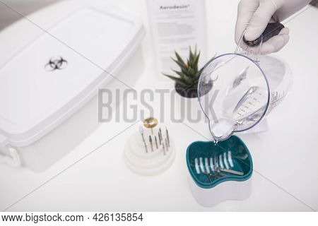 Cropped Close Up Of Manicurist Sterilizing Her Nail Drill Bits After Working