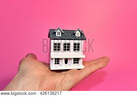 Miniature House In Hand On Pink Background. Home Buying Or Selling. Home For Family. Real Estate Inv