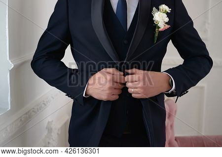 Groom In A Dark Blue Suit With A Tie And A Boutonniere Fastens A Button On His Suit Close-up