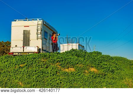 Woman Enjoying Trip With Motor Home, Holds Camera, Taking Travel Picture. Happiness, Vacation And Tr