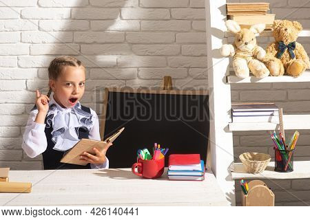 Funny School Girl Reading Book In Classroom At School. Portrait Of Lovely School Girl In Classroom A